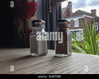 Glass slat and Pepper pot on cloth covered table - Stock Image