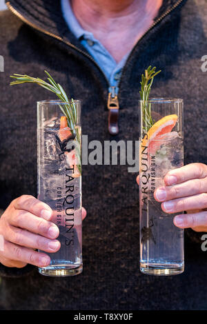 A customer holding two glasses of Tarquin's Cornish Gin and tonic at a pop up bar at Trebah Garden in Cornwall. - Stock Image