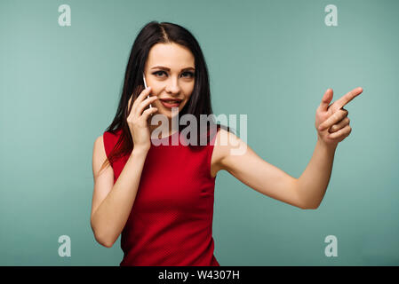 beautiful caucasian surprised young girl talking on her cell phone pointing isolated background - Image - Stock Image