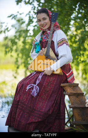 Young romantic woman in traditional russian clothes sits on the small dock near the lake, and posing for a camera - vertical portret - Stock Image