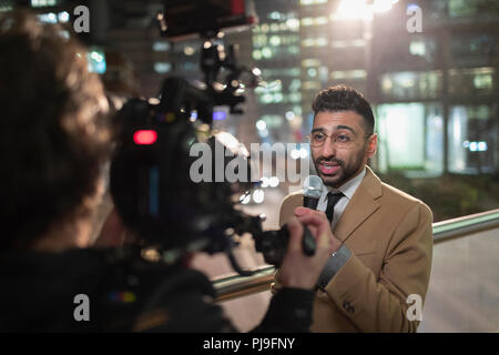 Male journalist and cameraman on urban sidewalk - Stock Image