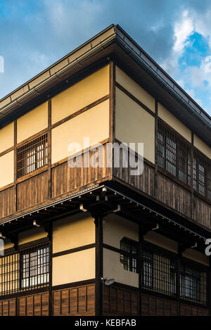 The sharp angles of the corner of a traditional wooden framed Japanese house at sunset - Stock Image