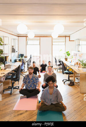 Serene creative business people meditating in office - Stock Image