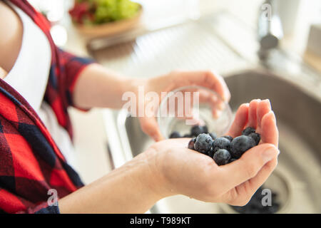 Woman is putting blueberries into the glass in the kitchen. - Stock Image