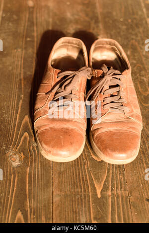 Old and well-worn brown leather shoes set against a rustic wooden background with copy space area for travel fashion - Stock Image
