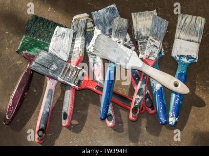 A pile of old, used paintbrushes with hard bristles and coated paint, ready to be thrown away. - Stock Image