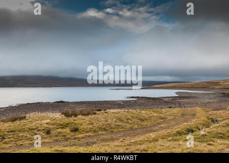 North Pennines AONB Landscape, a brief bright interval highlights the foreshore of Cow Green reservoir, Upper Teesdale on a dull November day - Stock Image