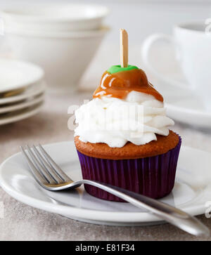 Spice cupcake with vanilla frosting decorated with a caramel apple for Thanksgiving Holiday - Stock Image