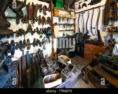Clog makers workshop showing the workbench with several anvils tools and clogs  at  Ryedale Folk Museum in Hutton le Hole North Yorkshire England UK - Stock Image