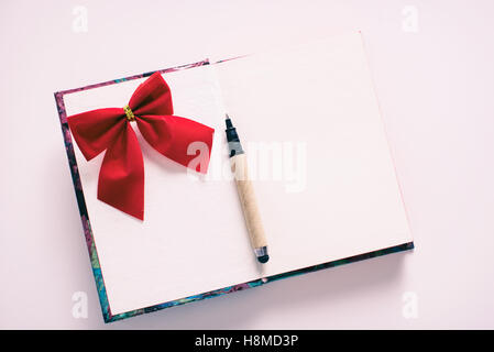Notebook with pen and a red ribbon - Stock Image