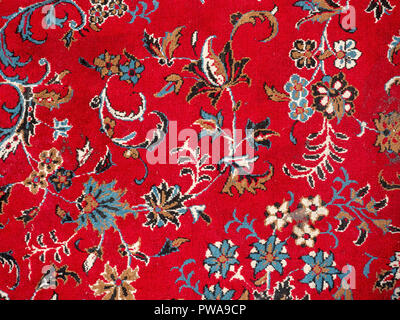 Red persian rug close up with floral design - Stock Image