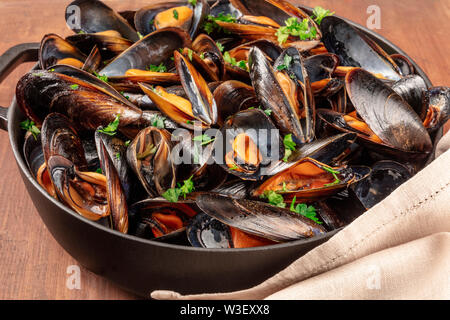 Marinara mussels, moules mariniere, in a large cooking pot, close-up view on a dark rustic wooden background - Stock Image