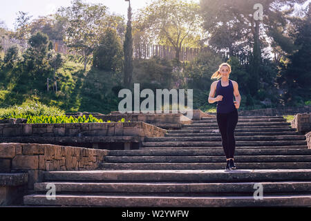 young sports woman running downstairs in the morning on the stairs of the park, morning workout outdoors, sports and healthy lifestyle - Stock Image