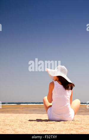 Young woman sitting back on the sand at the beach - Stock Image