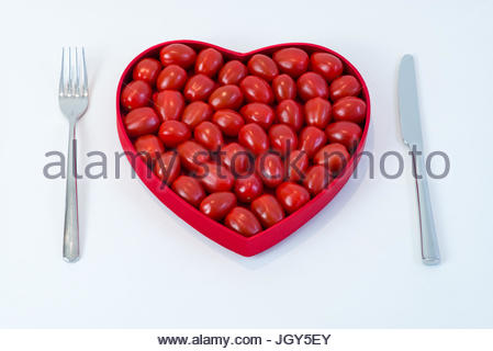 Cherry tomatoes in heart shaped container with knife and fork - Stock Image