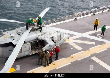 180828-N-JN023-0320 ATLANTIC OCEAN (Aug. 28, 2018) Sailors perform pre-flight checks on a MH-60S Sea Hawk on the flight deck of the Wasp-class amphibious assault ship USS Kearsarge (LHD 3) prior to flight operations during the Carrier Strike Group FOUR (CSG 4) Amphibious Ready Group, Marine Expeditionary Unit Exercise (ARGMEUEX). Kearsarge Amphibious Ready Group and 22nd Marine Expeditionary Unit are enhancing joint integration, lethality and collective capabilities of the Navy-Marine Corps team through joint planning and execution of challenging and realistic training scenarios. CSG 4 mentors - Stock Image