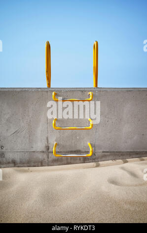 Steel ladder embedded in a concrete wall, conceptual picture. - Stock Image
