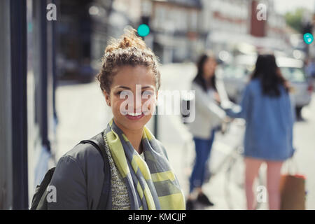 Portrait smiling young woman on sunny urban street - Stock Image