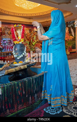 An anonymous  devout Hindu worshipper says a prayer to the Shiva lingam at a Hindu temple in South Ozone Park, Queens, New York. - Stock Image