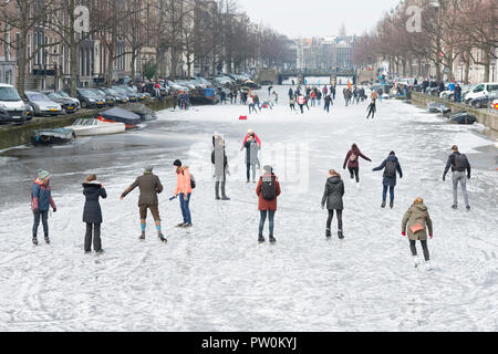 Ice on canal Keizersgracht, Amsterdam and ice skating people. A typical Dutch winter scene. - Stock Image