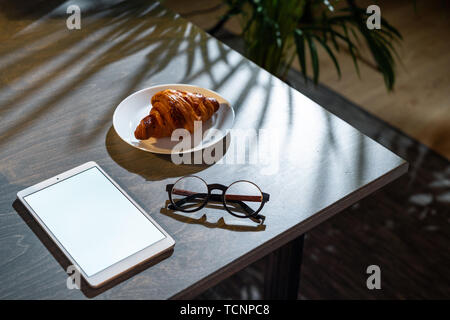 Close up of croissant, glasses and pad with blank screen on dark wooden table with tropic plant on background. - Stock Image