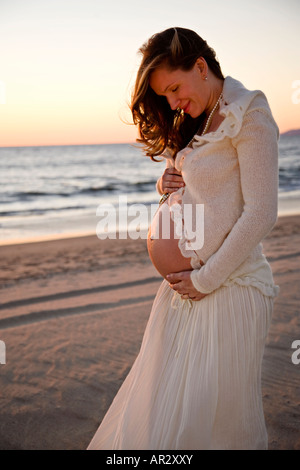 Pregnant woman holding her bare belly on the beach at sunset - Stock Image