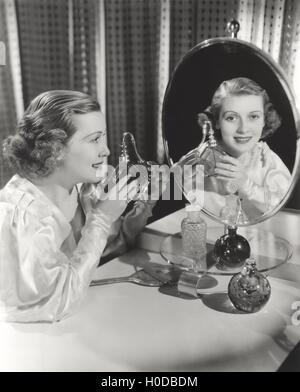 Reflection of woman holding perfume atomizer in mirror - Stock Image