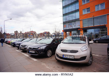Poznan, Poland - March 8, 2019: Row of parked cars on parking spots close by the Globis office building with Orange telecommunication shop on the Slow - Stock Image