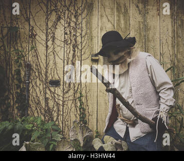 A scary evil scarecrow man is holding a stick with a monster burlap mask on his face standing against an old shed - Stock Image