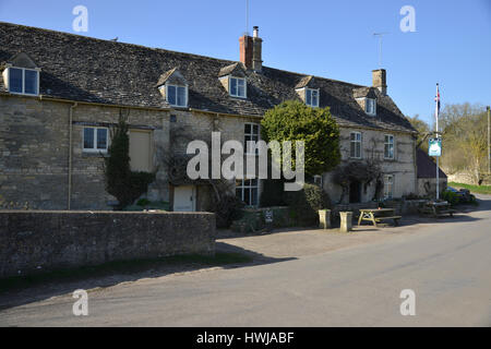 The Swan Inn in the Cotswold village of Swinbrook close to Burford lies beside the River Windrush - Stock Image