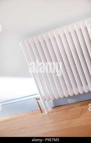 a white radiator in a  newly decorated room - Stock Image