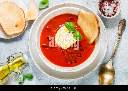 Tomato soup with mozzarella cheese, Basil and spices in a white plate. A thick, hearty dish, served with bread toast and olive oil. Selective focus - Stock Image