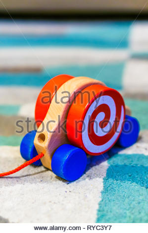 Blue wheeled headless wooden toy snail on a carpet. - Stock Image