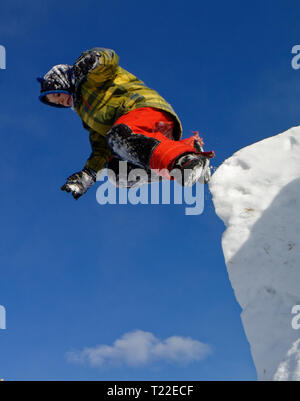 A young boy (6 yrs old) jumping from the top of a snow cliff - Stock Image