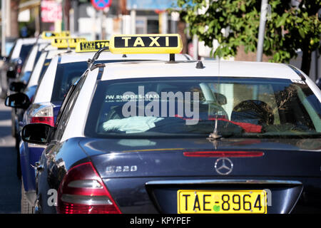 A row of similar liveried  taxi's or cabs waiting on a taxi rank for hire. All are displaying taxi signs and - Stock Image
