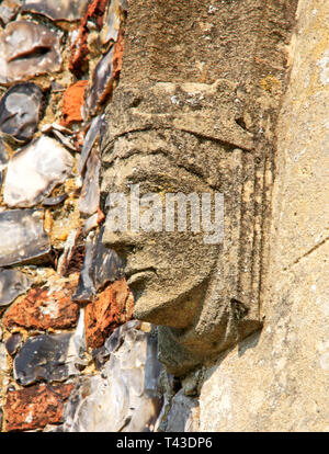 A carved stone head decoration at the base of the arch on the south porch of the Church of St Andrew at Wickhampton, Norfolk, England, UK, Europe. - Stock Image