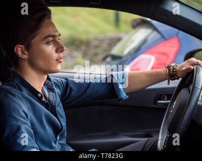 Handsome blue eyed young man sitting in his car, looking away - Stock Image