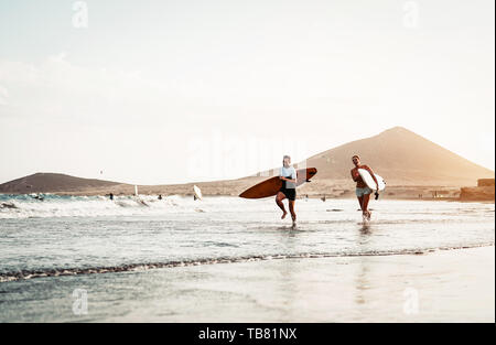 Happy surfer couple running with surfboards along the sea shore - Sporty people having fun going to surf together at sunset - Stock Image
