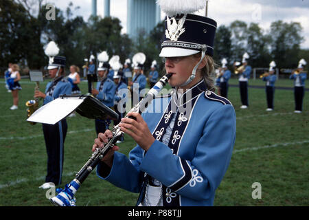 A girl a member of the marching band playing a flute - Stock Image