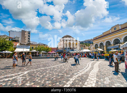 Local Greeks and tourists enjoy an afternoon shopping at Monastiraki Square near the base of Acropolis Hill on a summer day in Athens, Greece - Stock Image