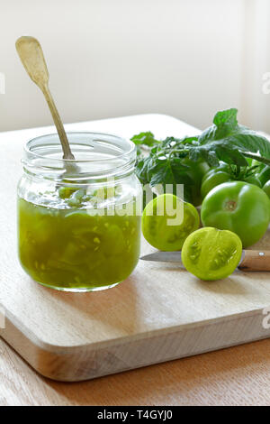 Green tomato jam or relish in a glass jar with vintage spoon, home canning concept - Stock Image