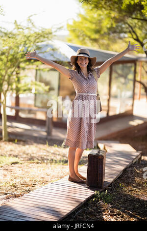 Senior woman standing with her arms wide open - Stock Image
