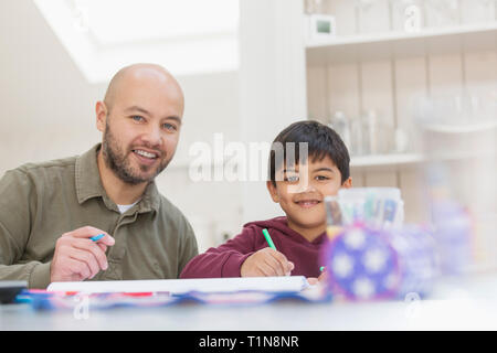 Portrait happy father and son coloring at table - Stock Image