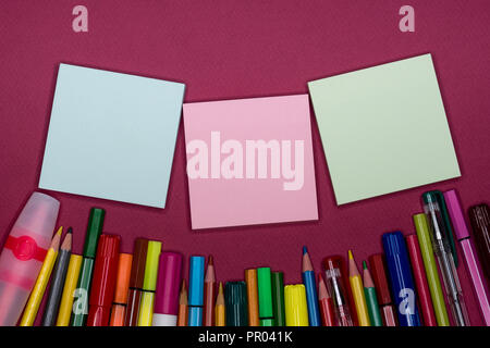 Directly above view of color pencils, blank sticky memo for text and design, purple background, work desk with copy space. - Stock Image
