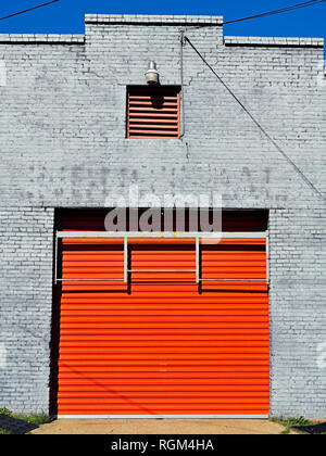 Bright colorful orange industrial roll top door on a painted brick building in Montgomery Alabama, USA. - Stock Image