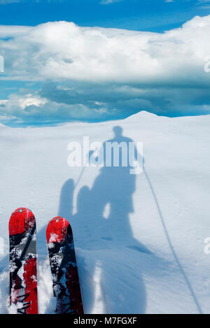A pair of touring skis and a shadow of the skier on the snow. - Stock Image