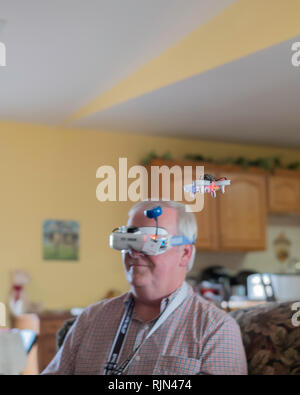 A 55 year old Caucasian man uses Fat Shark drone goggles to visualize his small EACHINE E10 mini UFO quadcopter drone flying inside a home. USA. - Stock Image