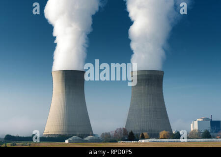 two power plant cooling towers steaming on dark blue sky background - Stock Image