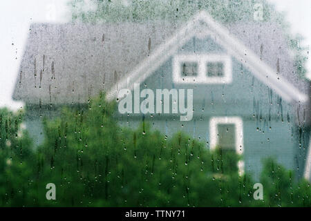 House seen through wet glass window - Stock Image