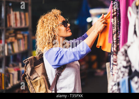 Cheerful traveler young blonde curly woman looking and choosing clothes at the used market during alternative vacation - shopping lifestyle concept fo - Stock Image